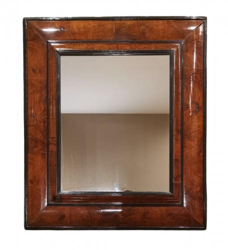 A Louis XIV walnut cushion-framed mirror  late 17th century, circa 1680.