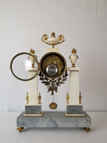 Horology  - A Louis XVI portico marble and gilt-bronze mantel clock.
