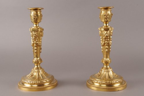 Lighting  - A late 19th century pair of candlesticks