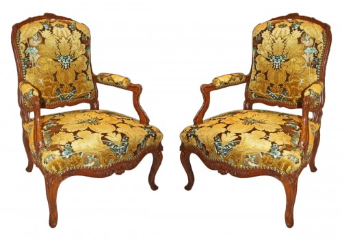 A pair of large Louis XV violin-shaped natural and carved-wood Fauteuils
