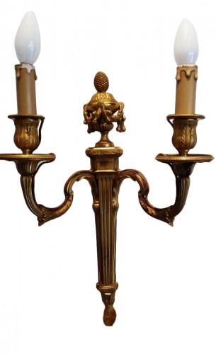 A pair of louis XVI ormolu two branch wall lights