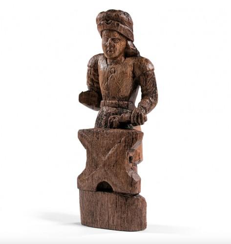 Wood sculpture depicting Saint Eloi as a blacksmith