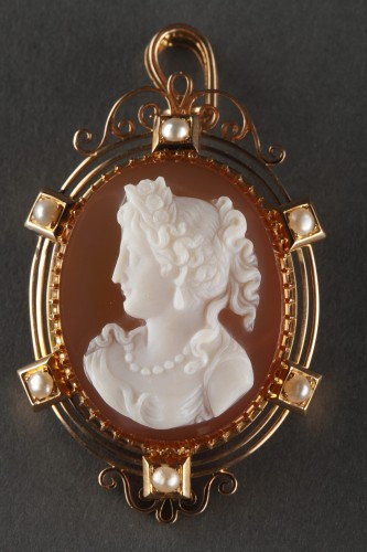 Antique Jewellery  - Cameo on orange-pinkagate featuring a young woman looking toward the left.