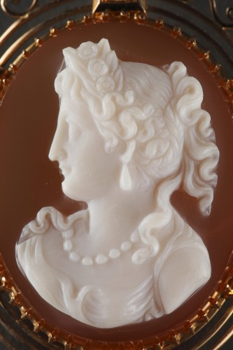 Antiquités - Cameo on orange-pinkagate featuring a young woman looking toward the left.