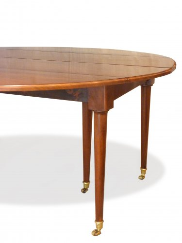 A Louis XVI solid mahogany extending dining table -