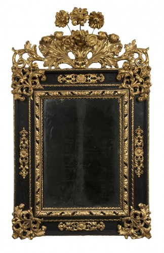 A late 17th century Italian blackened wood and Parcel Gilt Mirror