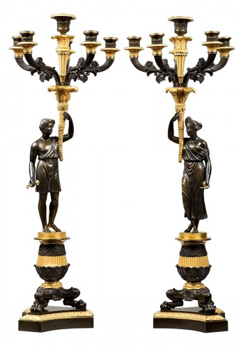 An empire patinated and gilded bronze pair of candelabras