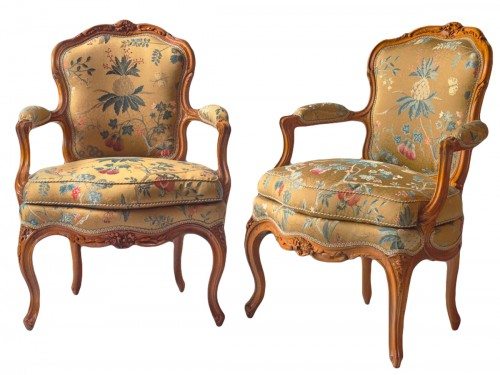 A pair of Louis XV walnut armchairs attributed to P. Nogaret