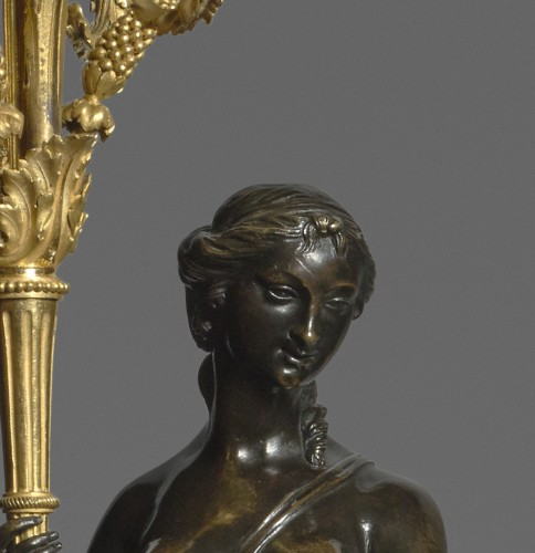 A pair of Louis XVI ormolu and patinated bronze three-lights candelabras -