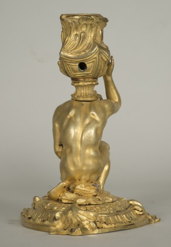 Gilt bronze candlestick depicting a man sat on a rock -