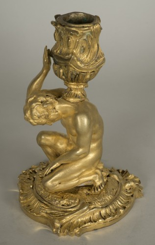 - Gilt bronze candlestick depicting a man sat on a rock