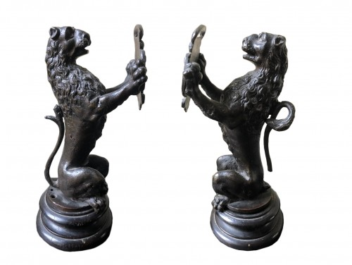 Pair of bronze lions holding a coat of arms