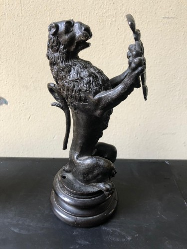 Pair of bronze lions holding a coat of arms -