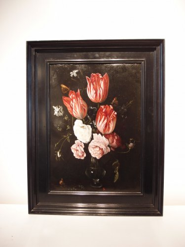 A bouquet of tulips and roses in a glass vase -