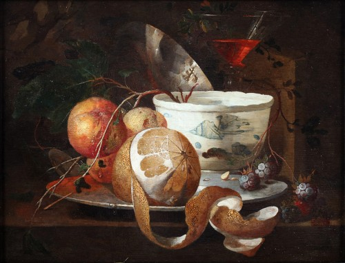 A still-life with a wan-li cup, an orange, a peeled lemon on a plate