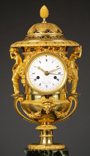 Clocks  - An Empire Suite of an Urn-shaped Mantel Clock and Two Vases