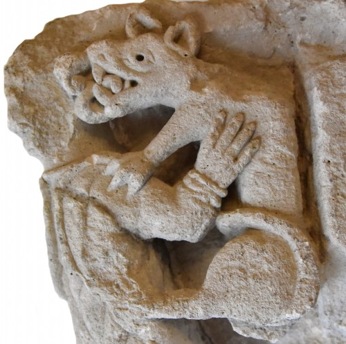 Romanesque sculpture representing a harpy devoured by a wolf, France 1150 -