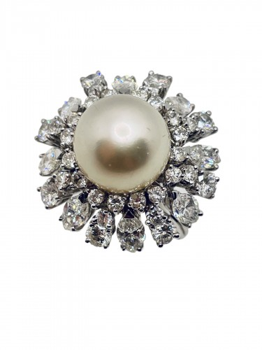 Gold ring center south sea pearl surrounding by diamonds .