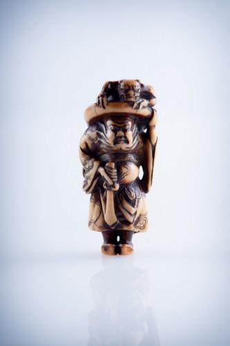 A Japanese ivory netsuke of a Shoki -