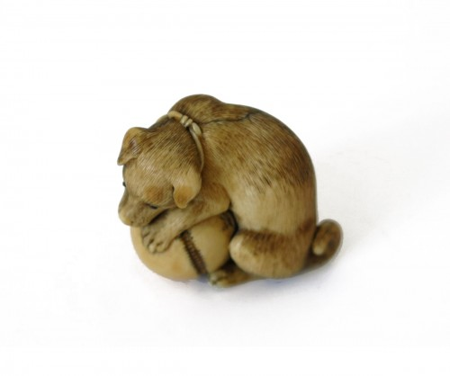 NETSUKE –  an ivory puppy seated, playing with a bell. Japan Edo
