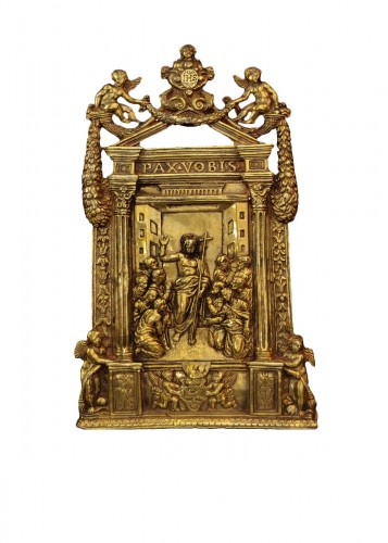 An elaborate gilt bronze pax of the Risen Christ dated 1557