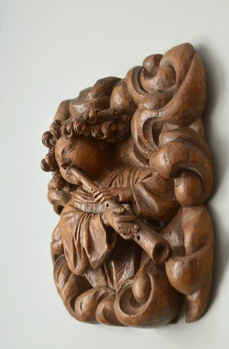 A superbly carved 15th century wood relief of an angel blowing a shawm -