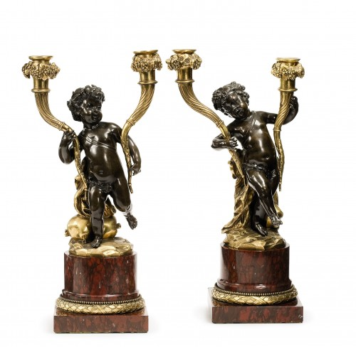 A pair of Louis XVI patinated and gilt bronze candelabra after a Clodion