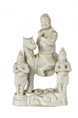 A Blanc de Chine figure of Guandi on his hors with two prayers, 18th centur